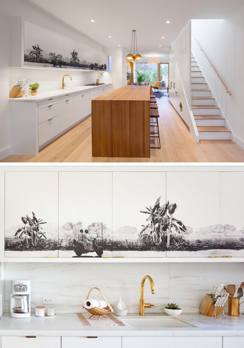Kitchen Ideas - A black and grey mural has been added to the upper cabinets in this white and wood modern kitchen, creating a central focal point for the open plan interior.  #KitchenIdeas #KitchenCabinets #Mural #Art #KitchenDesign #ModernKitchen