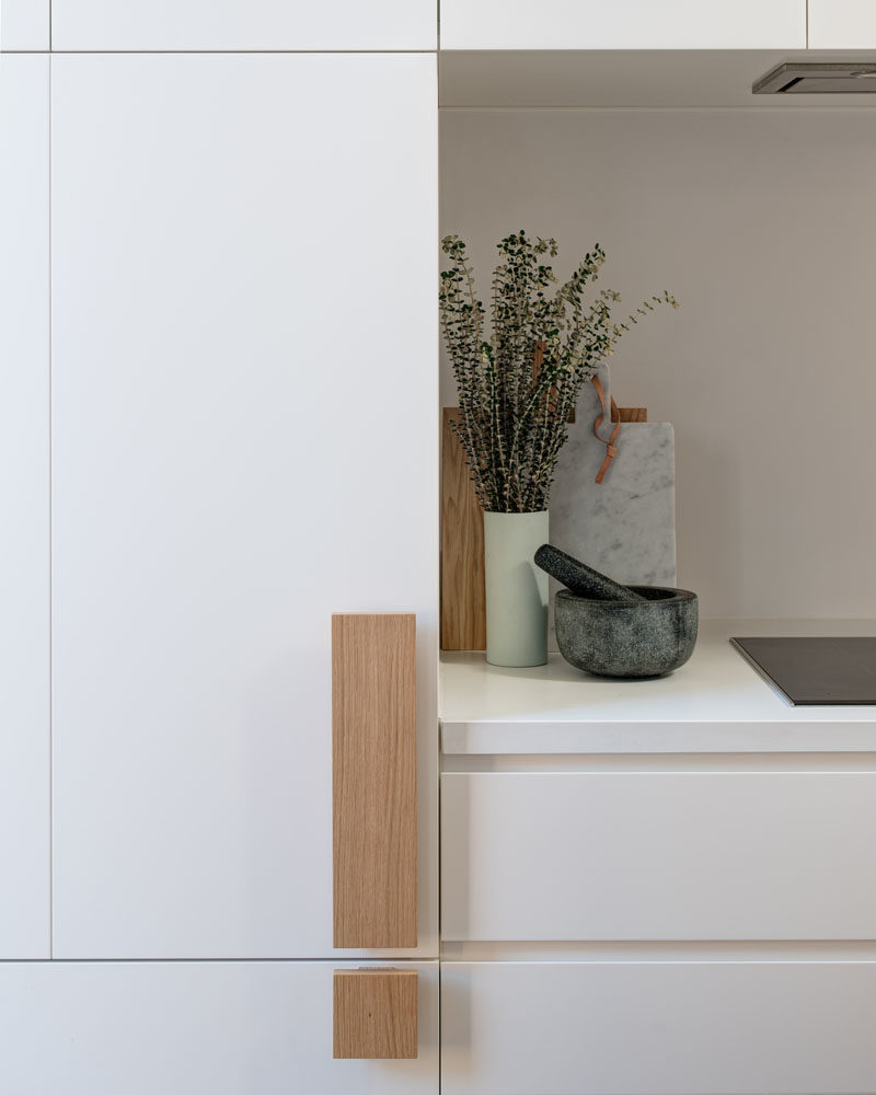 Kitchen Ideas - Oversized wood handles add a touch of nature to these minimalist white cabinets. #KitchenHandles #KitchenHardware #CabinetHardware