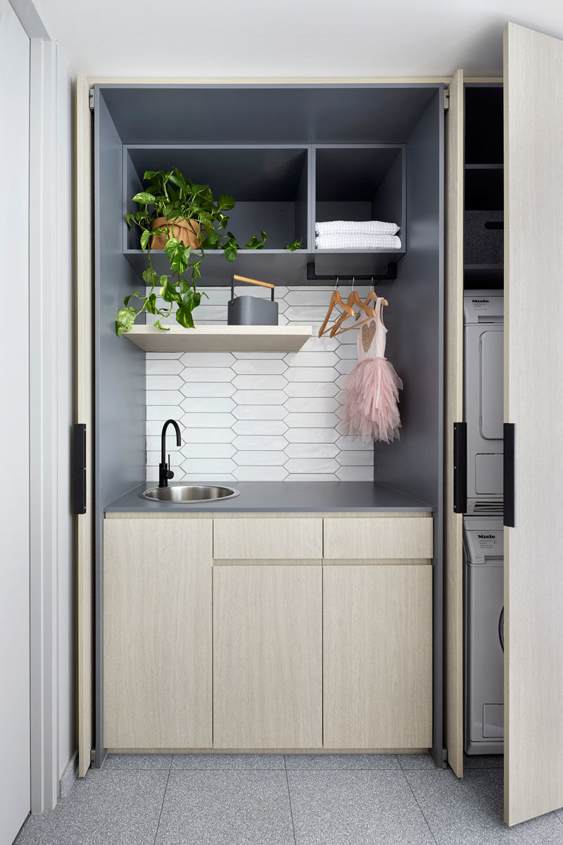 Hidden Laundry Ideas - In this modern white bathroom,  white picket tiles cover the walls, while the laundry is hidden away in wood cabinets opposite the vanity. #BathroomIdeas #PicketTiles #WhiteTiles #HiddenLaundry #Laundry #SmallLaundry