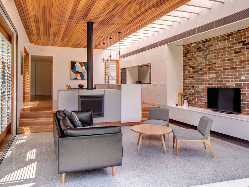 In this modern living room that features a time ceiling and recycled brick wall, there's fireplace and a few steps that provides separation between the living room and the dining room and kitchen. #LivingRoom #Fireplace #BrickWall #WoodCeiling