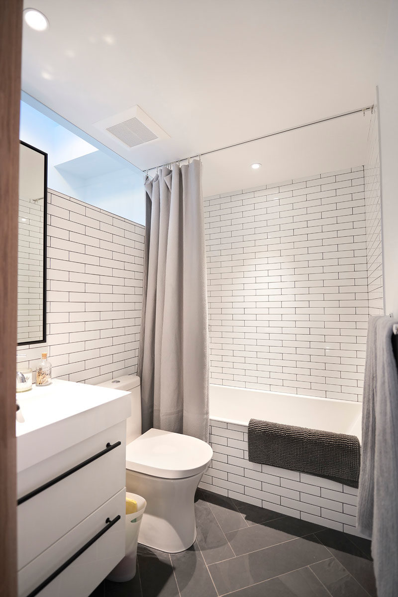 Bathroom Design Ideas - In this modern bathroom, white subway tiles line the walls, while a shower curtain hangs from a track in the ceiling. #BathroomIdeas #BathroomDesignIdeas #ShowerCurtain