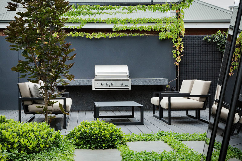 Landscaping Ideas - This modern outdoor lounge also has a dedicated BBQ area along the fence, with ivy growing above it. #LandscapingIdeas #OutdoorLounge #BBQ