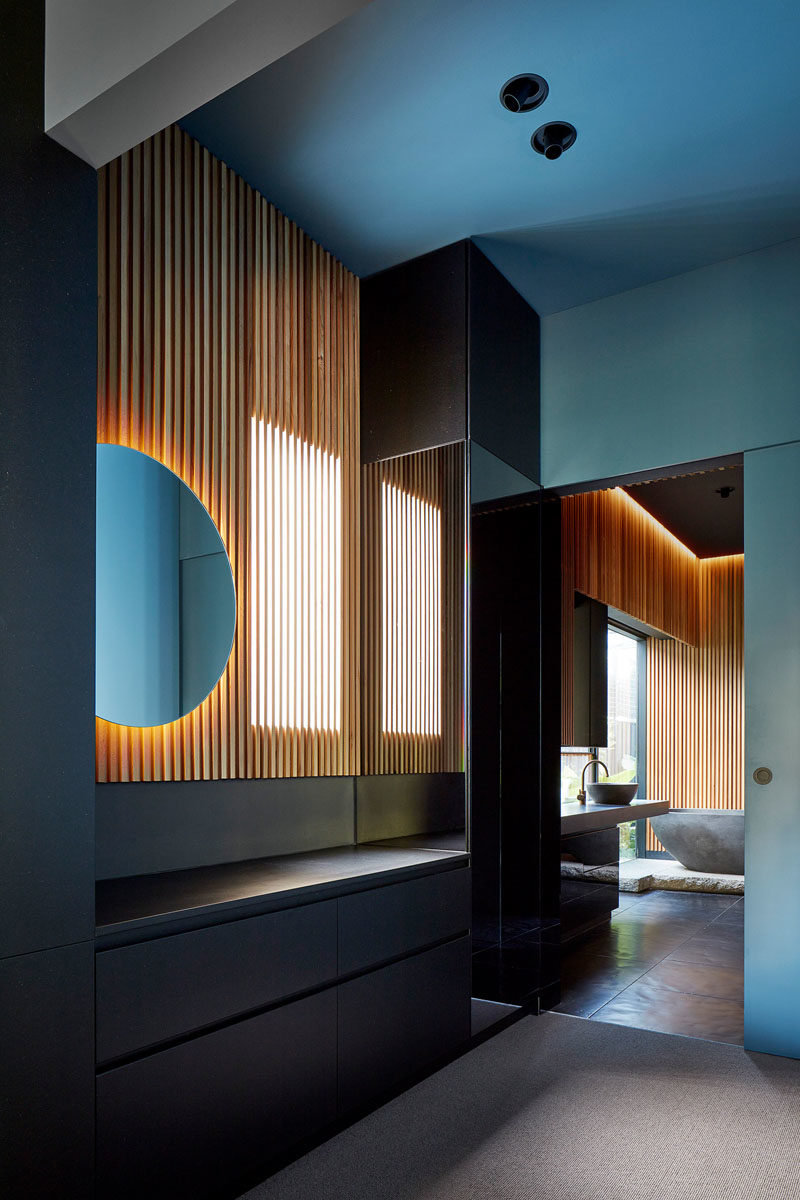 This walk-in closet that features a wood slat wall with a backlit mirror. A sliding door connects to the bathroom, that can also be accessed from the hallway. #BacklitMirror #WoodSlatWall #WalkInCloset
