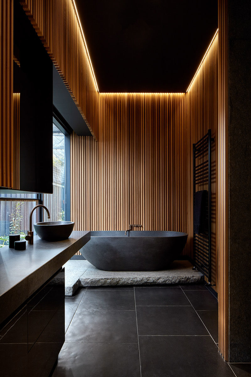 Bathroom Design Ideas - In this modern bathroom, hidden lighting creates a soft glow around the edges of the ceiling, while the wood slats create a backdrop for the black accents, like the bathtub, tile flooring, and window frame. #WoodSlats #BathroomDesign #ModernBathroom #WoodBathroom #BlackBathroom
