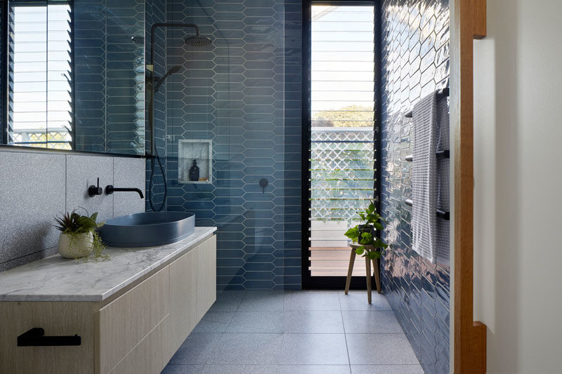 Bathroom Ideas - In this modern bathroom, blue picket tiles have been used to add color to the space, while in the shower, a built-in shelf complements the floating vanity countertop. #BlueBathroom #BathroomIdeas #TileIdeas