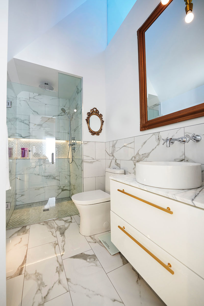 Bathroom Ideas - In this modern master bathroom, a skylight adds natural light to the space, while a walk-in shower has a built-in shelf and is enclosed behind a glass door. #BathroomIdeas #ModernBathroom