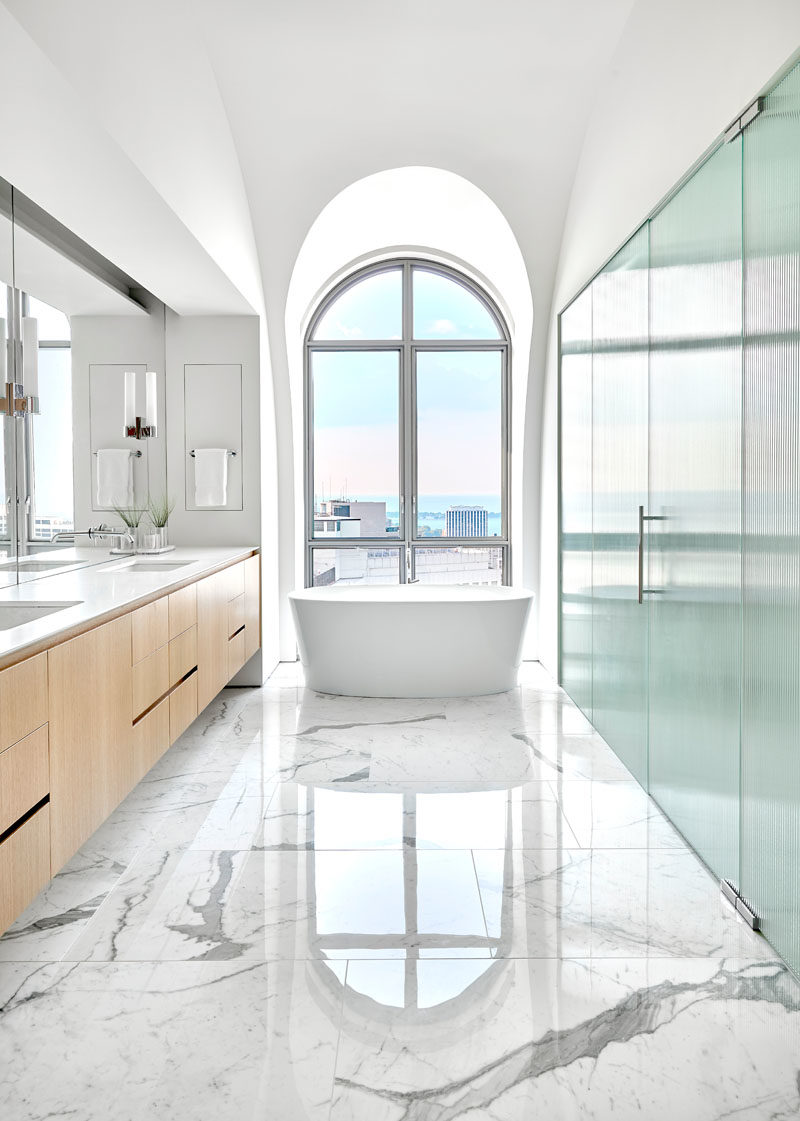 Bathroom Ideas - In this master bathroom, a freestanding bathtub sits directly in front of a large arched window, while a large vanity and mirror line the wall. #ModernBathroom #ArchedWindows #BathroomDesign