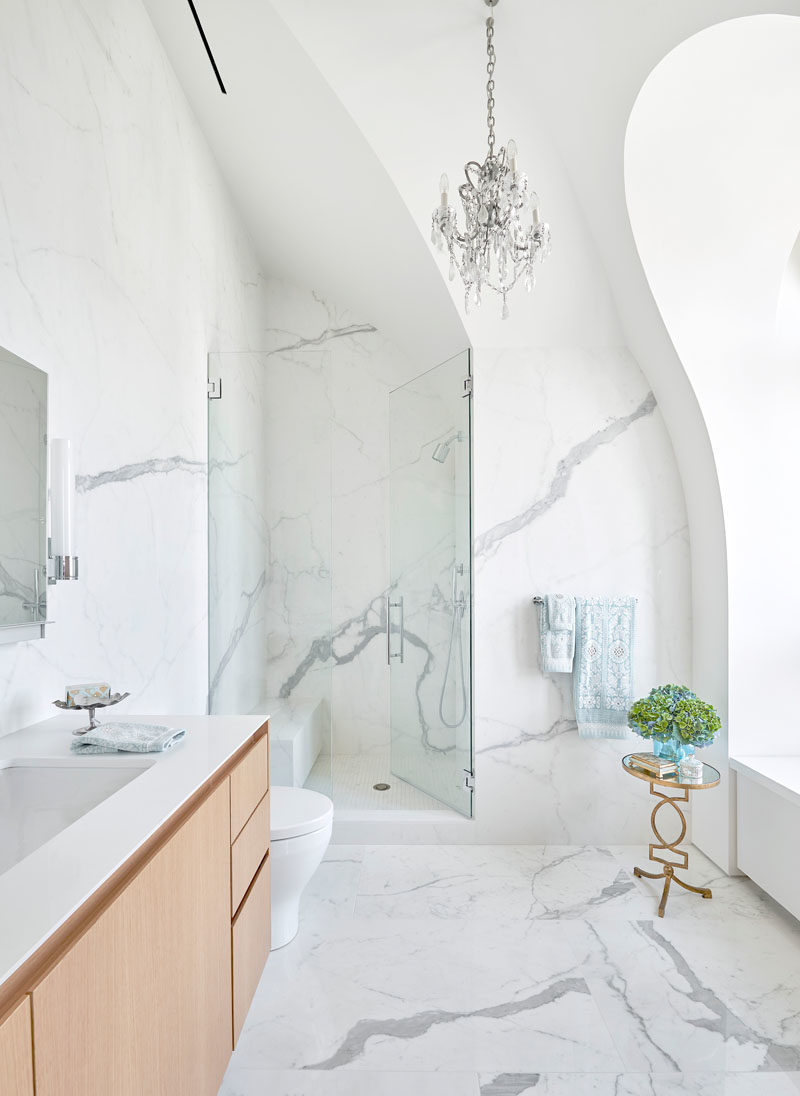 Bathroom Ideas - This modern bathroom has high arches and vaulted ceilings, while the shower has a built-in bench, and the shower door sits flush with the wall. #BathroomDesign #ModernBathroom