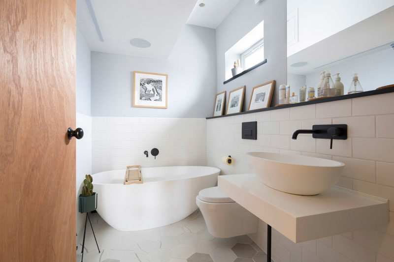 Bathroom Ideas - In this modern bathroom, the lower half of the room has been kept white, while a picture rail provides a place to display art and also acts as a small space for storing items above the vanity. #BathroomIdeas #ModernBathroom #BathroomDesign