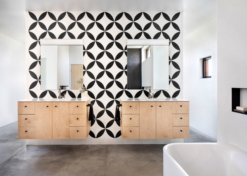 Bathroom Ideas - In this modern ensuite bathroom, black and white patterned tiles create a bold statement, and provide a backdrop for the floating wood vanities. #BathroomIdeas #BathroomDesign #PatternedTiles #FloatingVanity