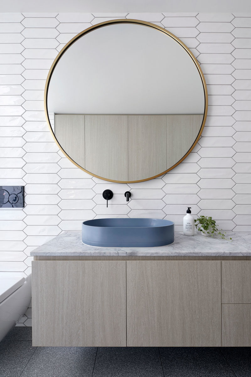 Bathroom Ideas - In this modern white bathroom,  picket tiles cover the walls, while the laundry is hidden away in wood cabinets opposite the vanity, and in the shower, there's a floor-to-ceiling window with views of a tiny garden at the side of the house. #BathroomIdeas #PicketTiles #WhiteTiles #HiddenLaundry #Windows