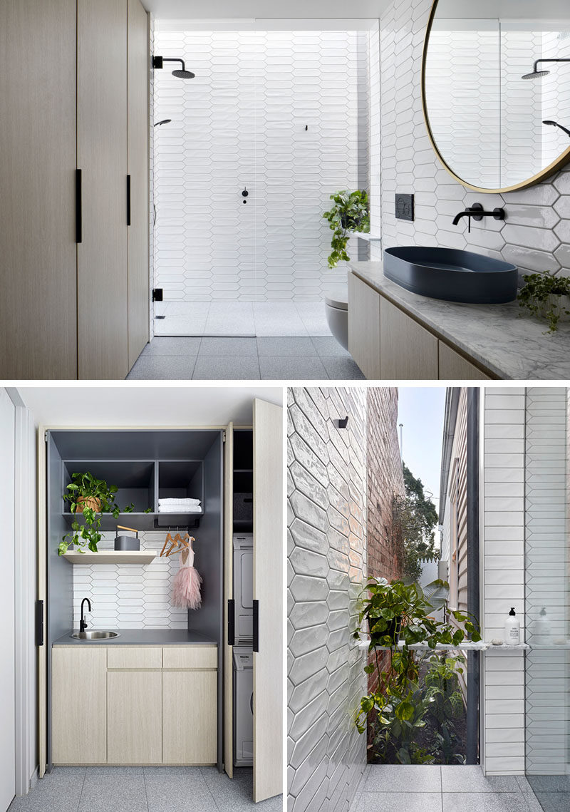 Bathroom Ideas - In this modern white bathroom,  white picket tiles cover the walls, while the laundry is hidden away in wood cabinets opposite the vanity, and in the shower, there's a floor-to-ceiling window with views of a tiny garden at the side of the house. #BathroomIdeas #PicketTiles #WhiteTiles #HiddenLaundry #Windows