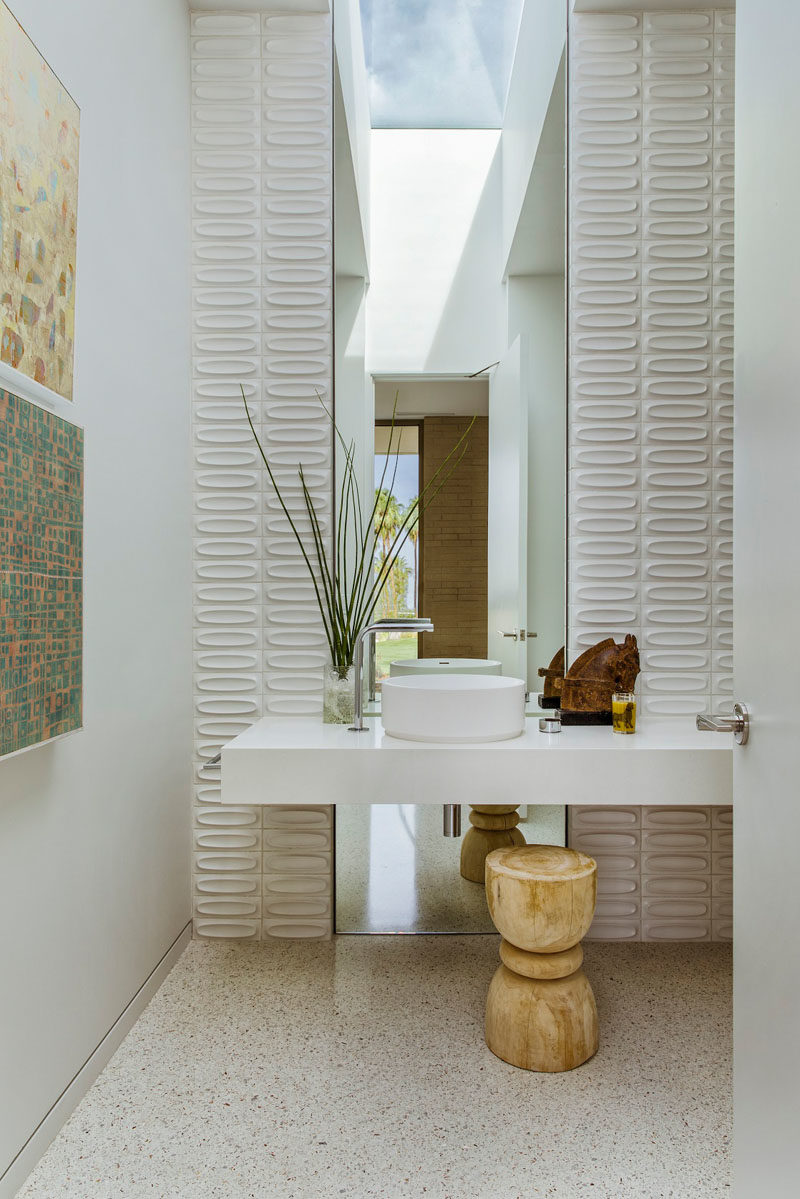 This modern bathroom features a tall mirror that reflects the light from the skylight, while tiles on either side add a textural element to the room. #ModernBathroom #Skylight #BathroomDesignIdeas