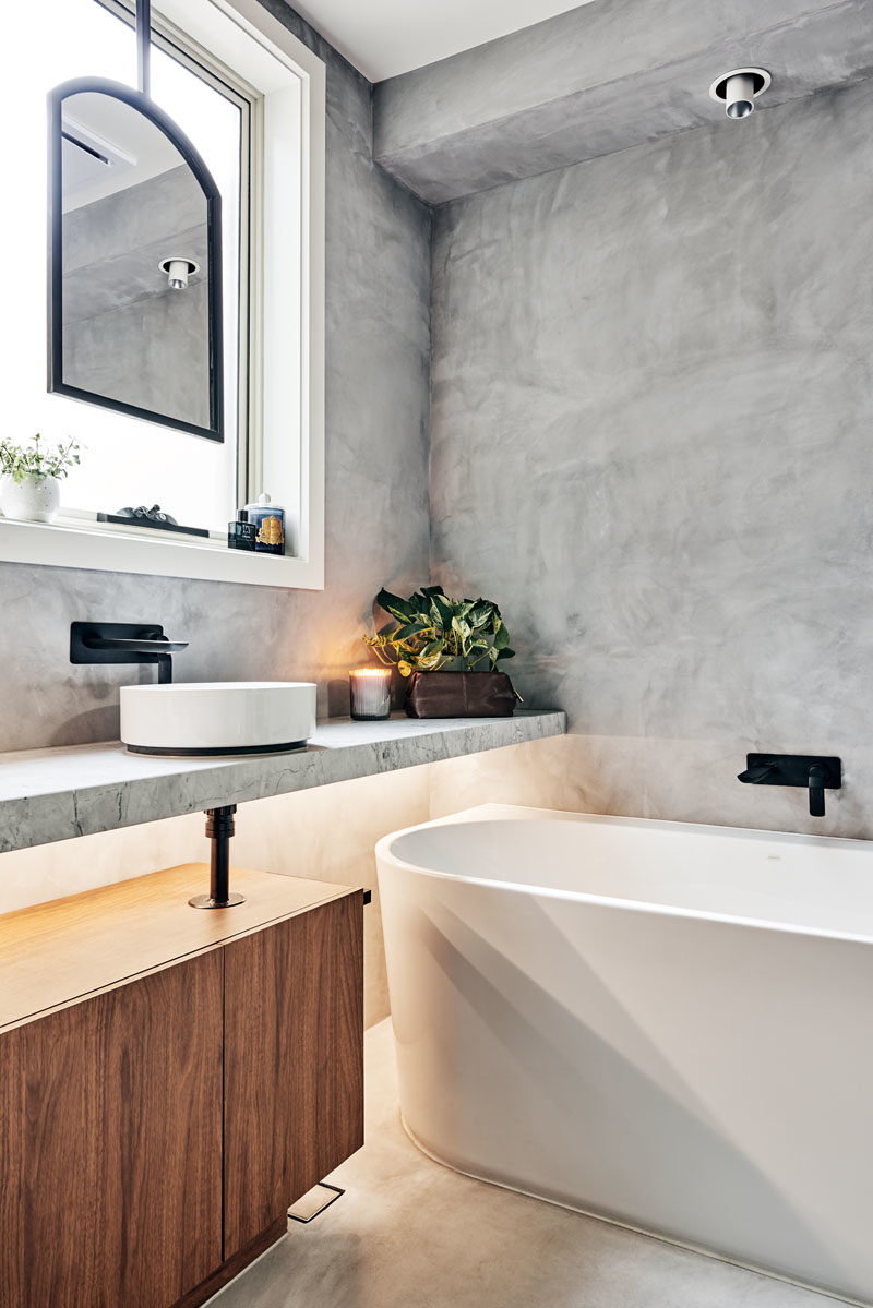 Bathroom Ideas - A matte black metal framed custom mirror suspended in front of a window, allowed the designers to maintain natural light and ventilation, while the white bathtub slightly tucked under a floating vanity bench, helped to o achieve the ultimate desired luxury of a soaking bath.  #BathroomIdeas #ModernBathroom