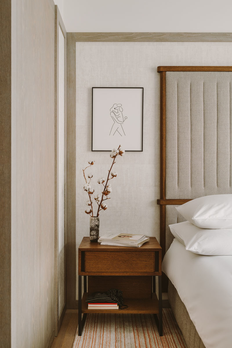 Bedroom Ideas - Simple furnishings,  such as a wood framed upholstered headboard, a wood side table, and minimal line art, have been included in this modern bedroom to create a calm atmosphere. #BedroomIdeas #BedroomFurniture #ModernBedroom