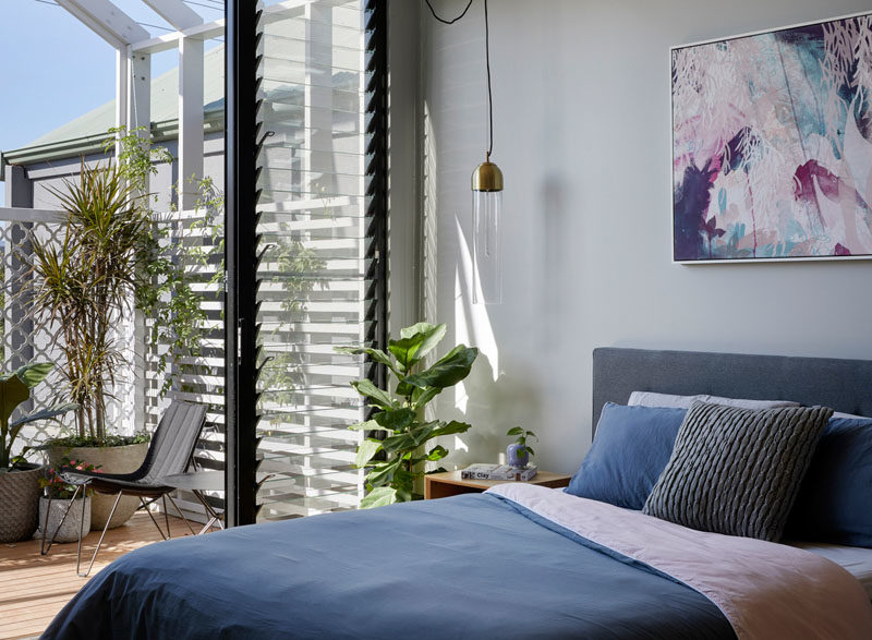 Bedroom Ideas - This modern bedroom opens up to the balcony with views of the backyard. Louvre windows allow the movement of air even when the door's closed. #BedroomIdeas #ModernBedroom #LouvreWindows #Windows