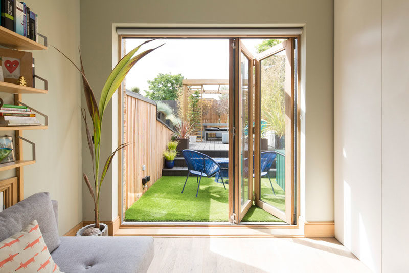 Door Ideas - This modern guest bedroom has wood-framed folding glass doors that open to the updated yard. #GuestBedroom #DoorIdeas #FoldingDoors