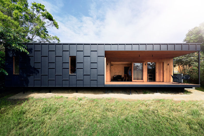 House Siding Ideas - The exterior of this modern house is covered in black fibre cement sheets with matching black battens, that create dimension and define the window locations. #ModernHouse #BlackSiding #Architecture #HouseSidingIdeas