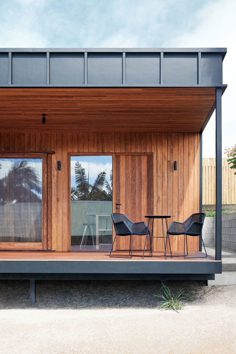 This small black and wood house has a covered porch off the living room and kitchen. #CoveredPorch #Deck #ModernArchitecture