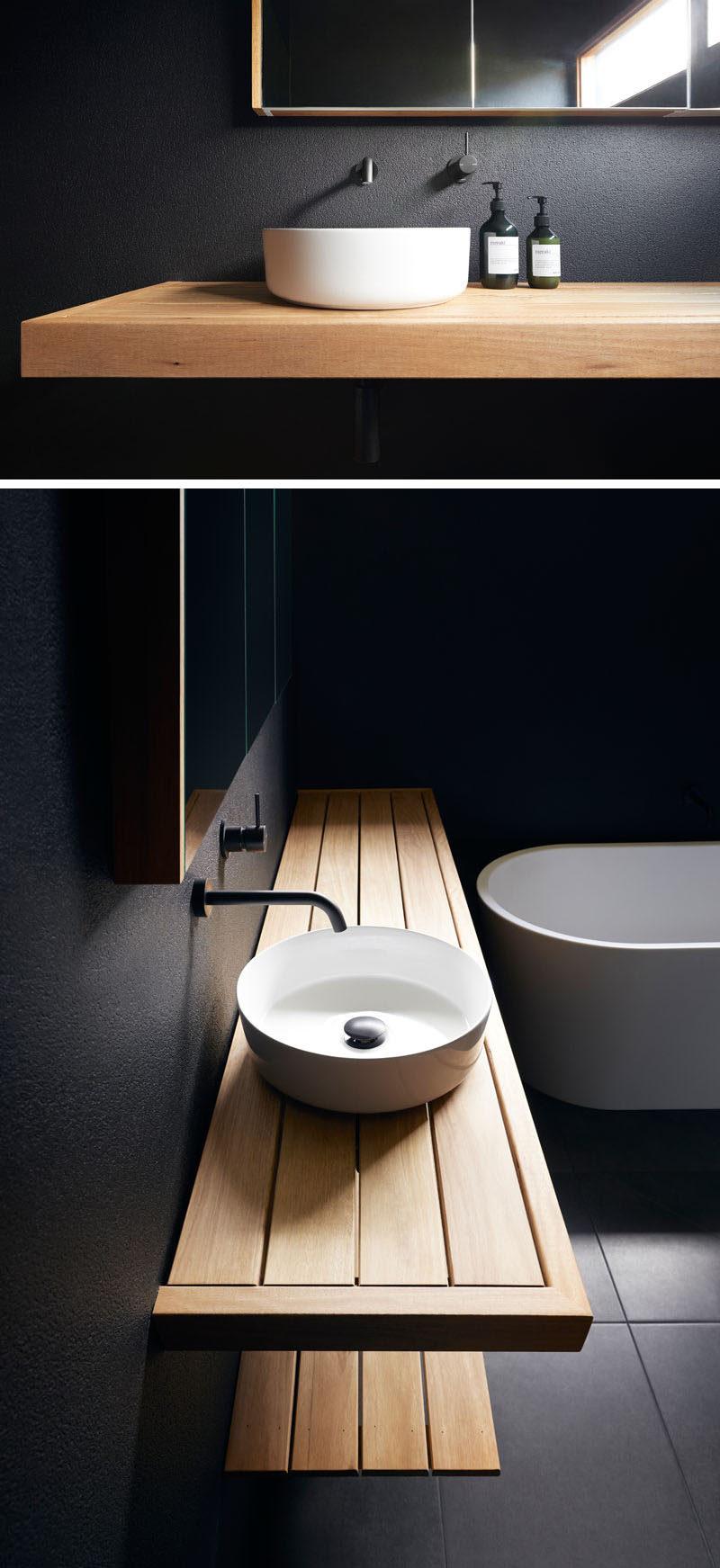 This modern bathroom has matte black walls, a wood vanity, and a white basin and bathtub. #BlackBathroom #ModernBathroom