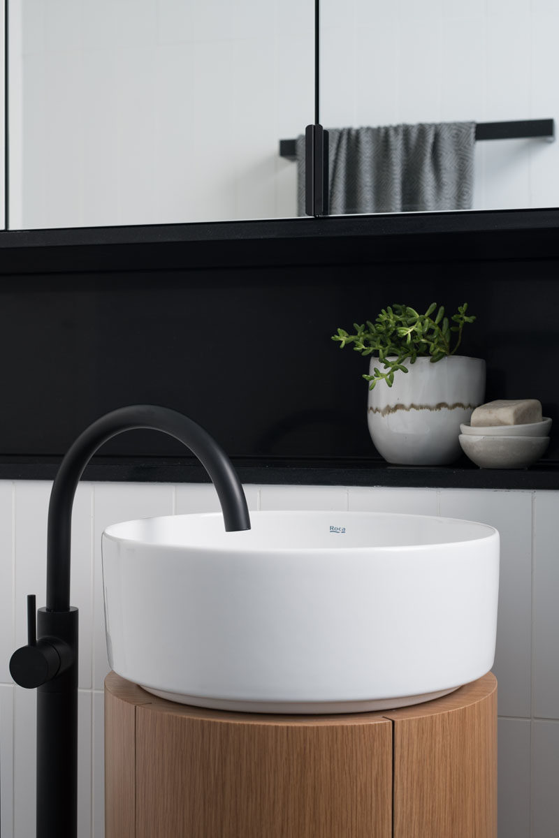 Bathroom Ideas - This modern bathroom has been designed with a minimalist pedestal sink, a walk-in shower, and black accents. #BathroomIdeas #BathroomDesign #ModernBathroom