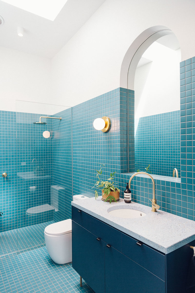 Bathroom Ideas - This modern bathroom features bright blue small square tiles, a skylight, and a curved mirror, fulfilling the home owners' request of an interior that's fun, curvy, colorful, and full of light. #BathroomIdeas #BathroomDesign #BlueBathroom