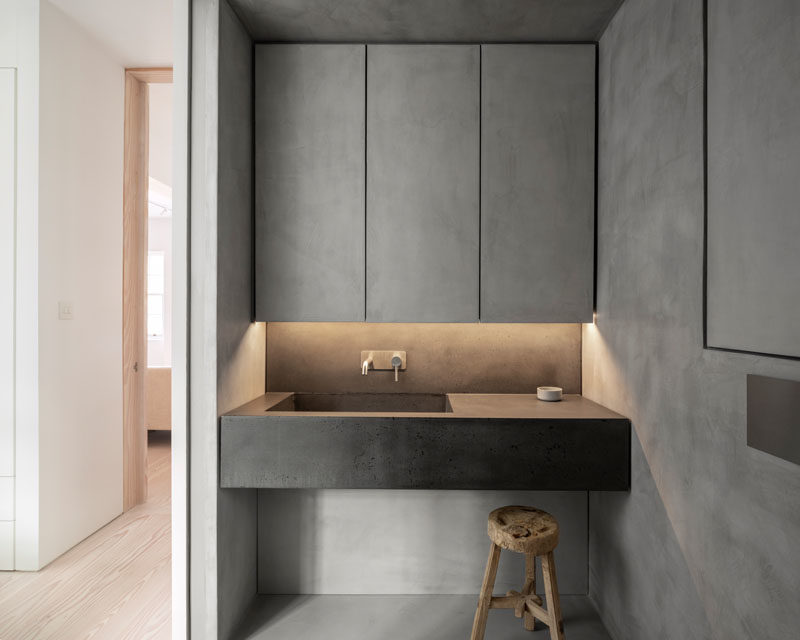 Bathroom Ideas - This modern bathroom has a seamless microcement finish, that's featured on the walls, floor, ceiling, and cabinetry, while a bespoke concrete vanity units has an integrated sink and brushed stainless steel fixtures. #BathroomIdeas #ModernBathroom #Microcement #ConcreteBathroom