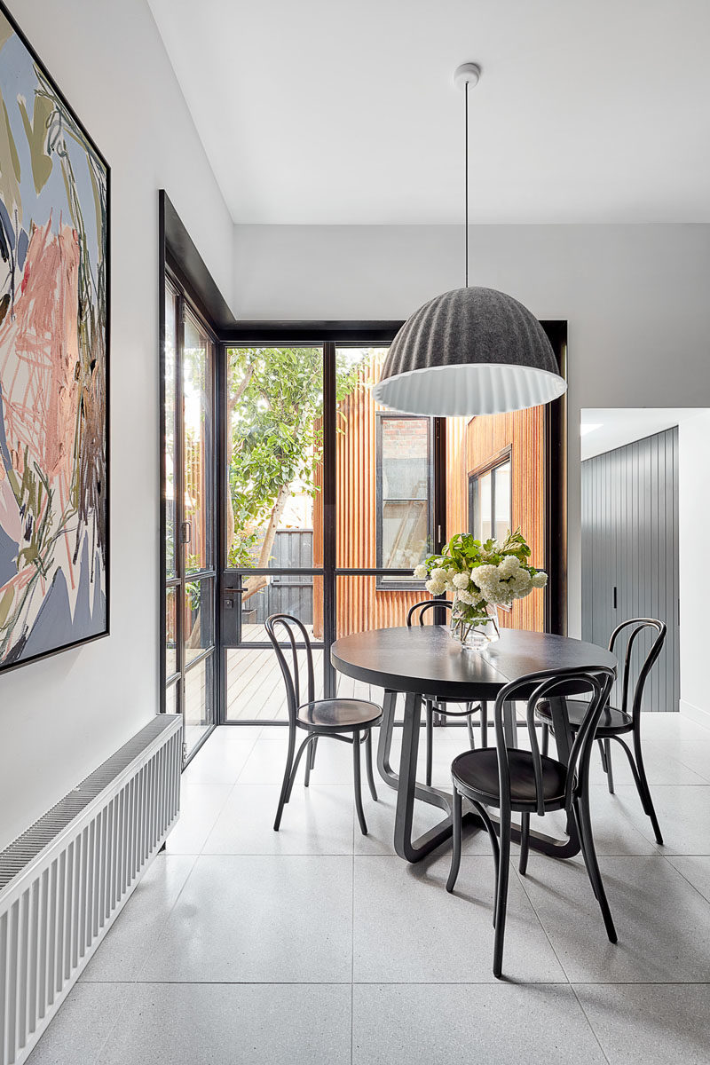 Dining Room Ideas - This modern dining area has been furnished with a round black table that's anchored in the open space by a large grey and white pendant light. #DiningRoomIdeas #InteriorDesign