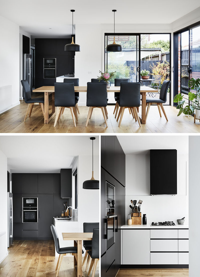 This modern interior features a large 8 person dining table, and a minimalist black and white kitchen. #ModernInterior #ModernDiningRoom #ModernKitchen #BlackKitchen
