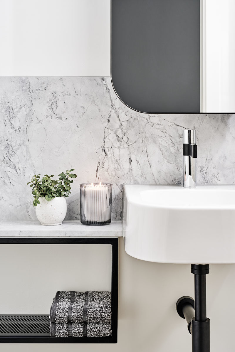 Bathroom Ideas - In this modern bathroom, a white vanity has been combined with grey stone, and black accents. #BathroomIdeas #BathroomDesign #ModernBathroom
