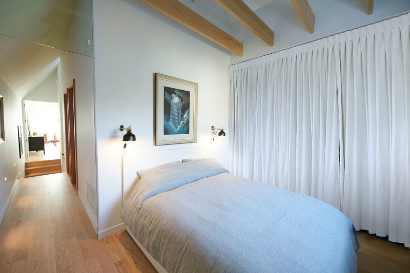 In this modern guest bedroom, furnishings have been kept minimal and a curtain lines the wall, while wood beams have been left exposed. #BedroomDesign #BedroomIdeas