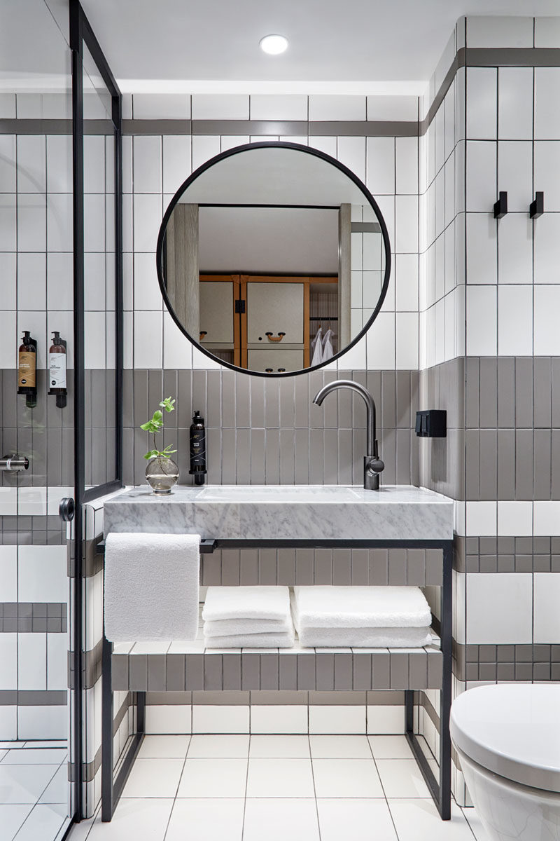 Bathroom Ideas - In this modern bathroom, grey and white tiles have been accented by black elements, like in the vanity, shower frame, mirror, and wall hooks. #ModernBathroom #BathroomIdeas #BlackBathroomAccents