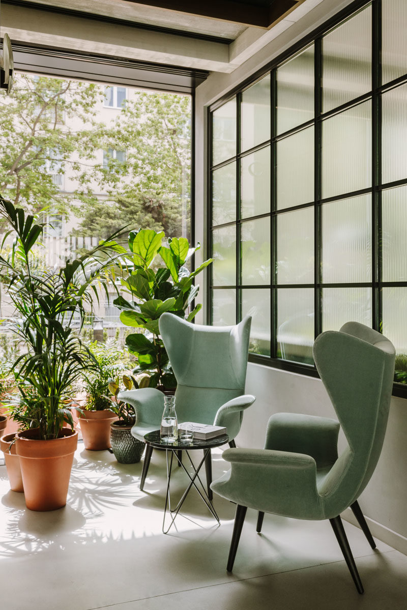 Decor Ideas - Green armchairs and potted plants sit beside a black-framed wall of windows, creating an almost tropical appearance. #DecorIdeas #Seating #Plants #Windows