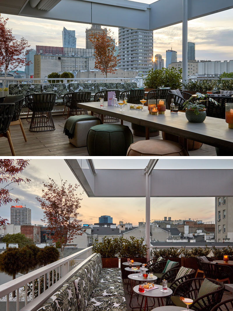 This modern rooftop cocktail bar has an almost tropical appearance, with leaf-print upholstery, wood flooring, and plants. #TropicalDesign #RooftopBar #Restaurant