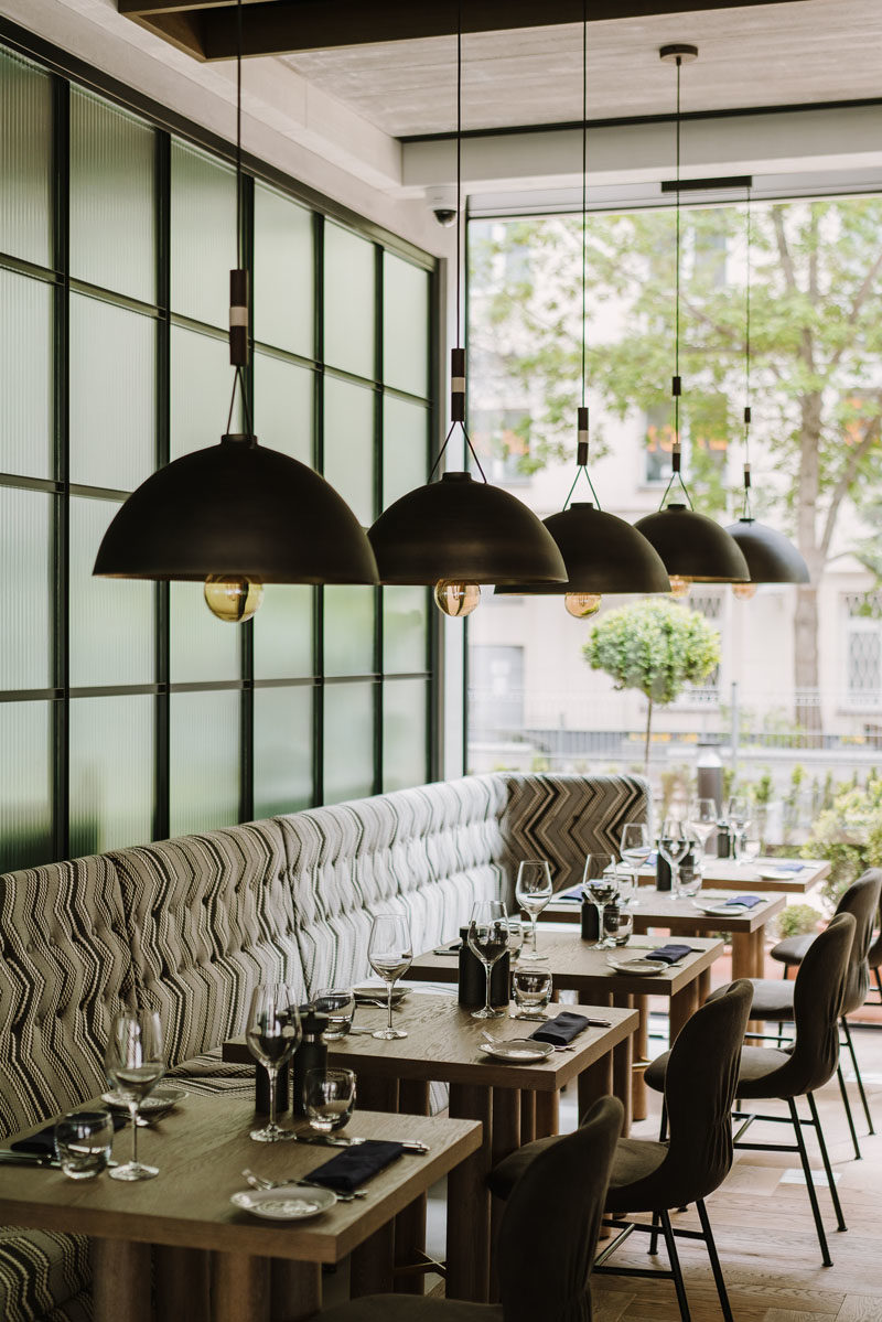 Restaurant Ideas - In this modern hotel restaurant, furnishings such as booths, banquette seating, and long communal wood tables, have been included to create a more rustic dining experience. #RestaurantIdeas #RestaurantDesign #InteriorDesign #Seating