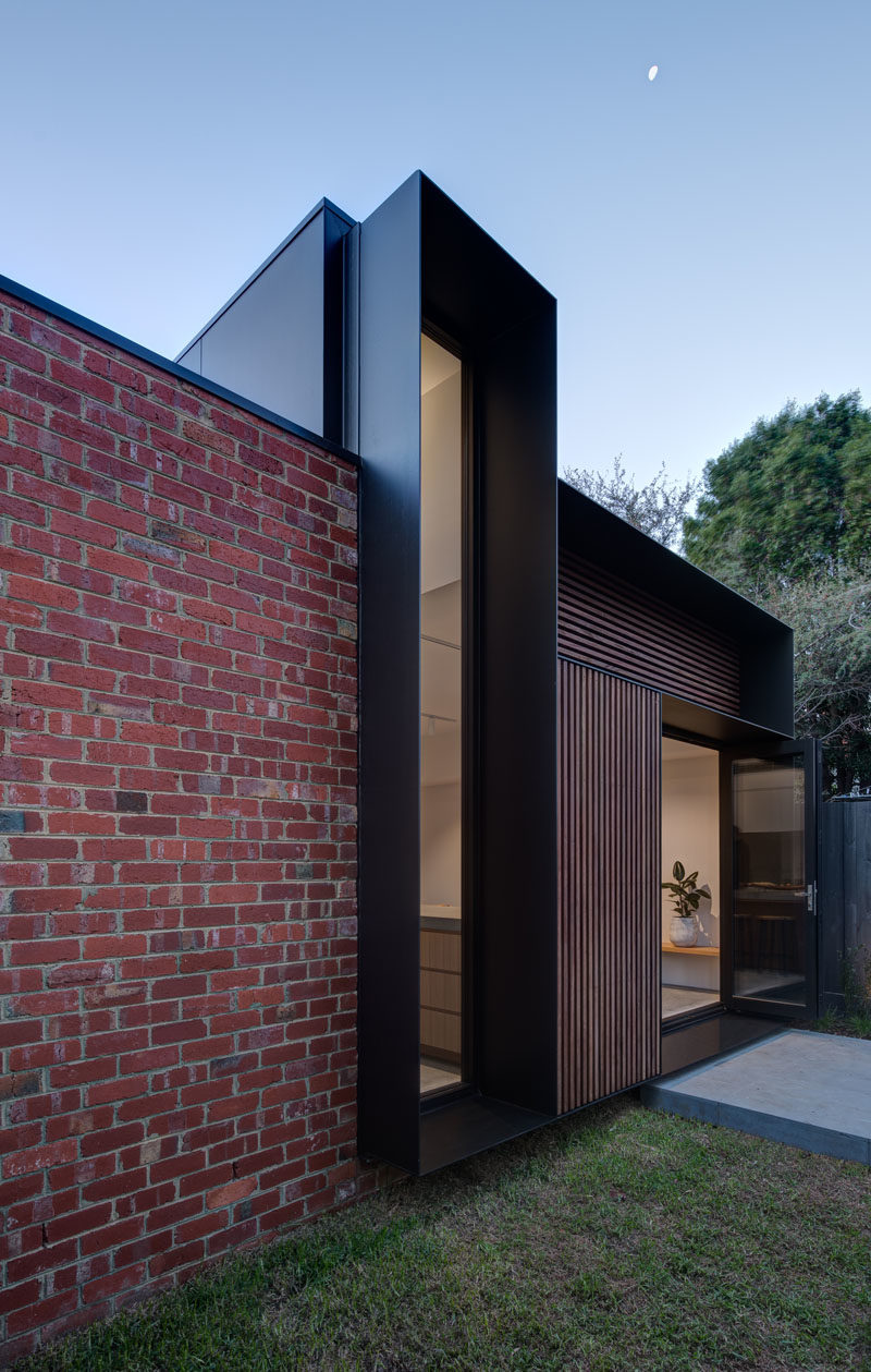 Window Ideas - This modern vertical window with a deep black steel frame, measures in at over 14 feet (4.5m) high and frames the large gum tree on the rear property. #WindowIdeas #WindowDesign
