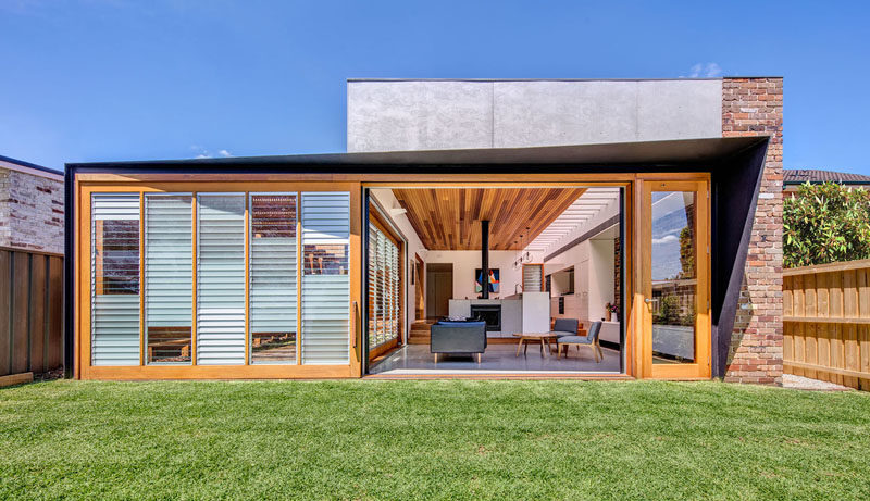 Door Ideas - This modern addition has an oversized sliding glass door, that contains a mix of opaque, clear and frosted glass louvres to allow the family to control air, light and privacy. #Doors #SlidingDoor #DoorIdeas #House Addition