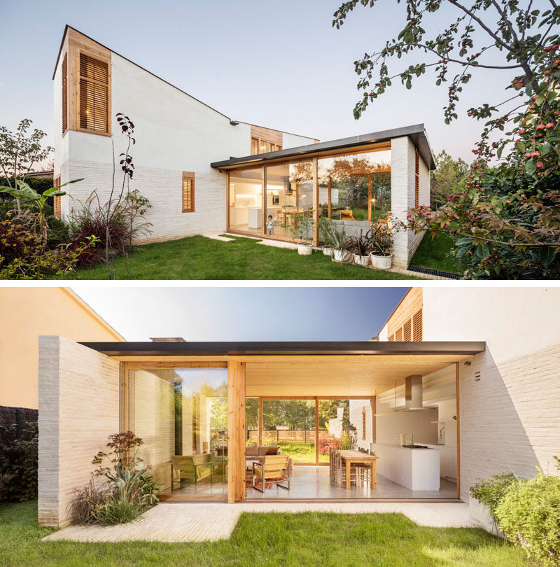 The horizontal component of this modern house has large wood-framed sliding glass walls that open to the garden on both sides. #GlassWalls #SldiingGlassDoors