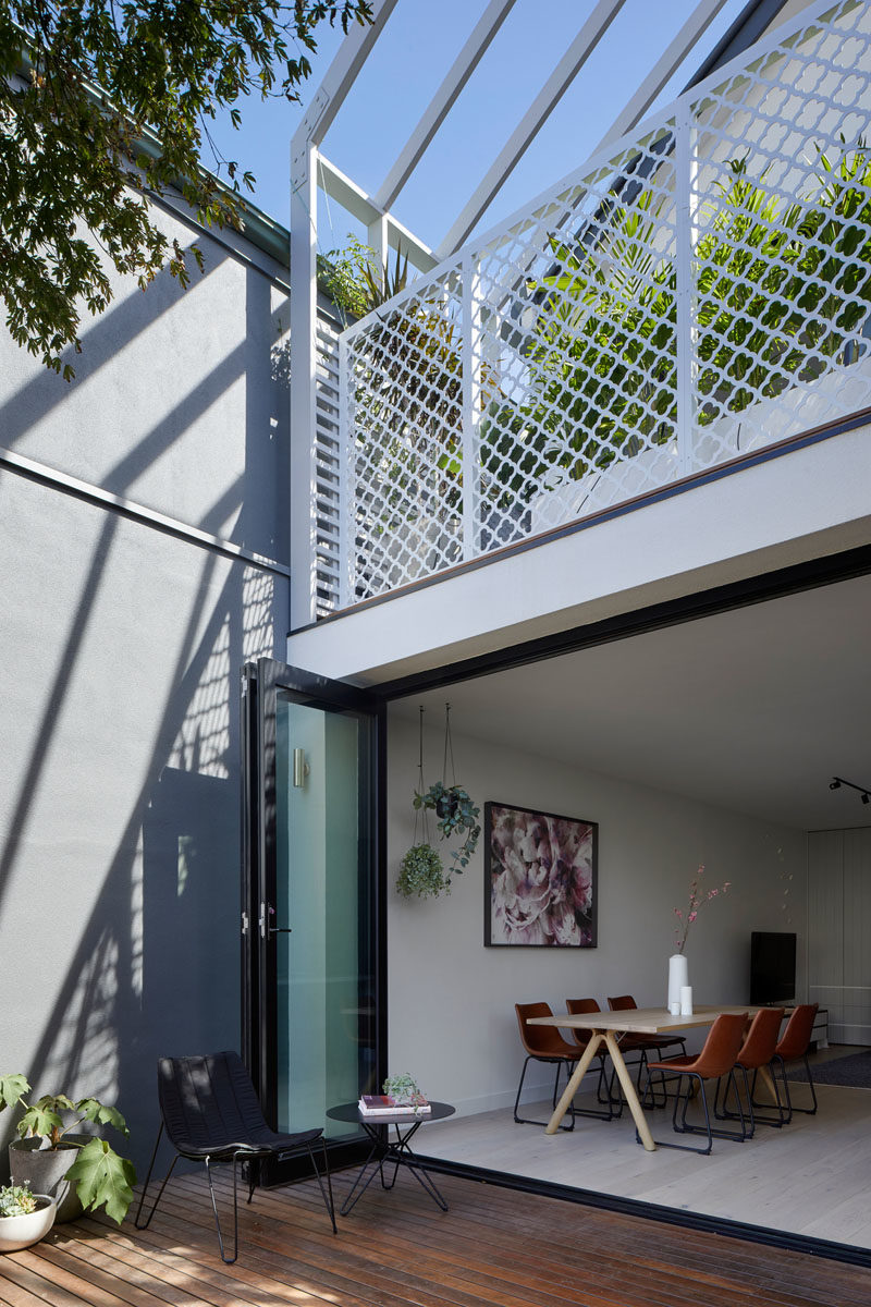 Folding doors connect the interior spaces of this renovated house with a wood deck, creating an indoor / outdoor living environment. #FoldingDoors #Deck