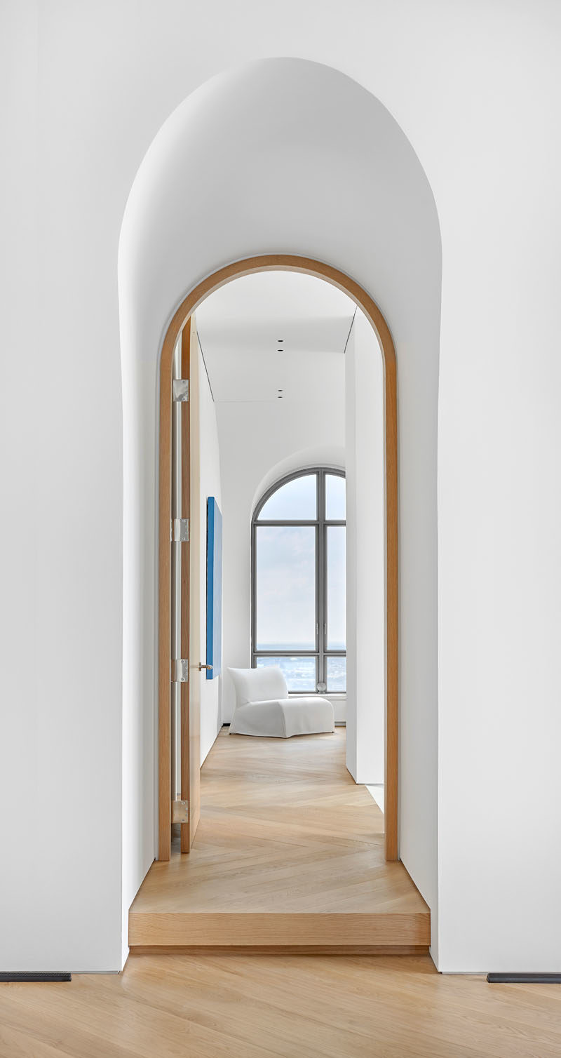This modern penthouse apartment features vaulted ceilings, arched doorways and windows, and oversized oak flooring. #Windows #ArchedDoorway #VaultedCeiling
