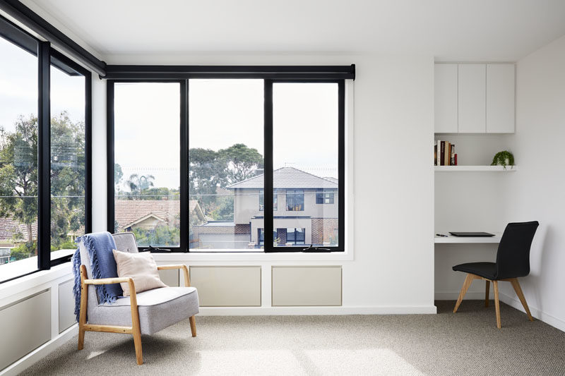 The windows on the second floor of this modern house provide views of the neighborhood, and make this room bright and airy. A desk with a shelf and storage cabinet has been built into a small alcove in the corner of the room. #SmallDesk #Windows #BlackFramedWindows