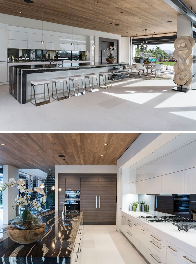 Kitchen Ideas - In this modern kitchen, a large island provides ample countertop space and room for seating, while a mirrored backsplash reflects the view, and a wood ceiling adds warmth to the open floor plan. #KitchenIdeas #ModernKitchen #LargeKitchenIsland