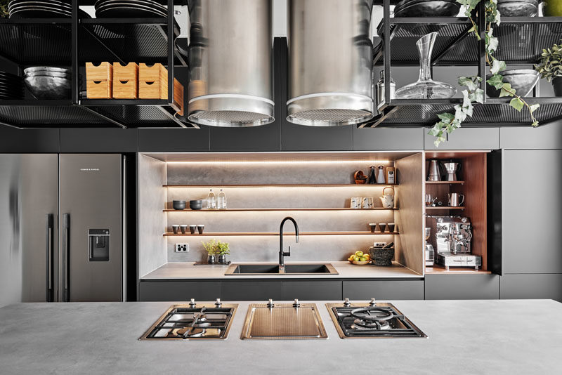 Kitchen Ideas, Stainless steel elements, metal shelving surrounding exposed exhaust vents, and a heavy use of greys, charcoals and blacks, make this modern kitchen bold, masculine, and industrial. #ModenKitchen #KitchenIdeas #ModernIndustrial