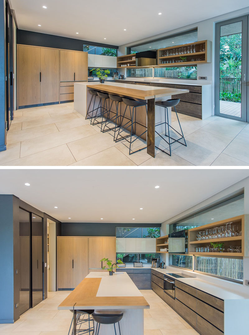 In this modern kitchen, the centrally located island has been designed to accommodate seating, white open shelving along one wall shows off the glassware collection. #ModernKitchen #KitchenDesign #KitchenIdeals