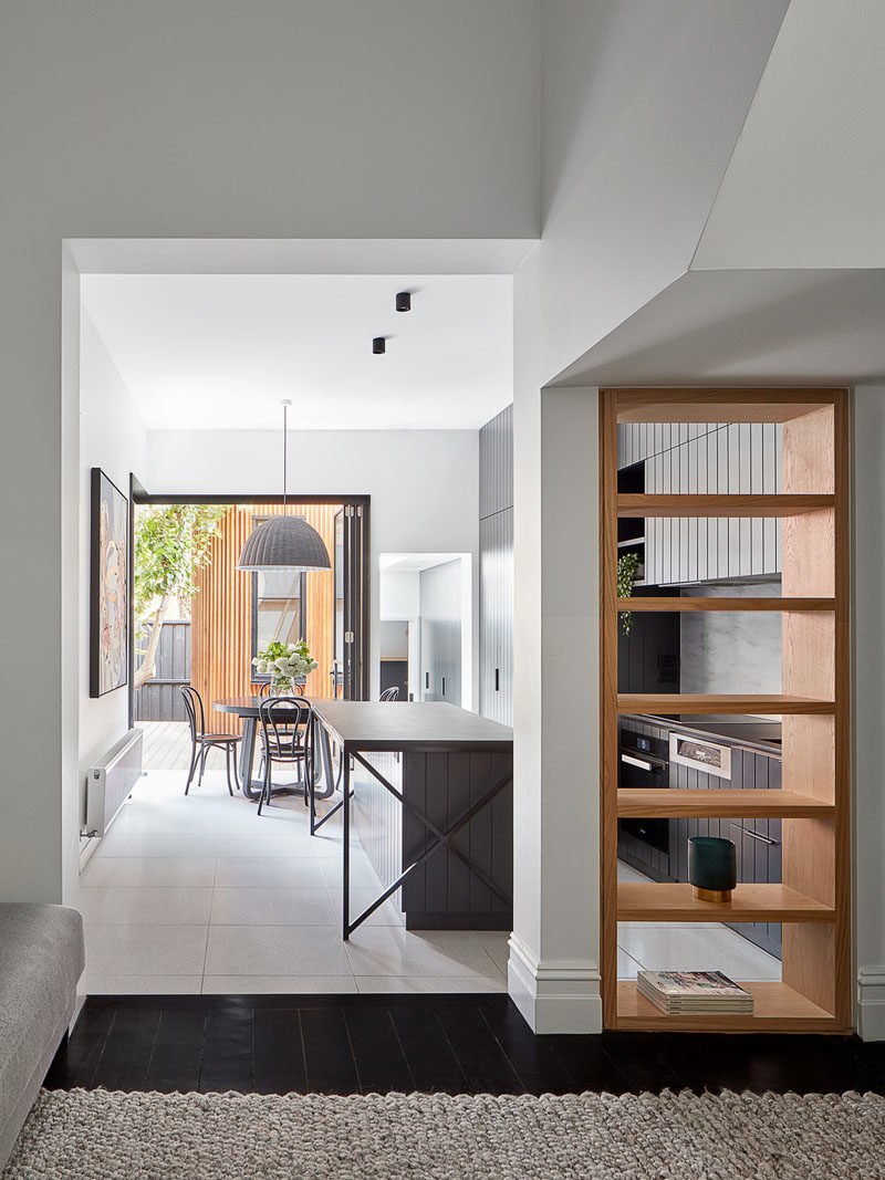 Shelving Ideas - From the front hallway of this renovated house, you're able to see the kitchen through an open bookshelf that's been built into the wall. #Bookshelf #ShelvingIdeas #WoodShelf #OpenShelf