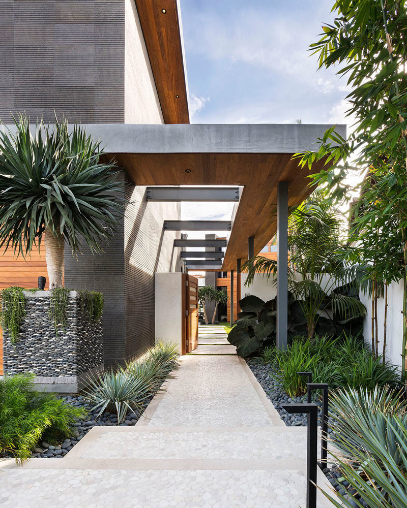 Landscaping Ideas - A partially covered path at the side of this modern house guides visitors through the gate and into the home. #Landscaping #Modernlandscaping #ModernPath #LandscapingIdeas