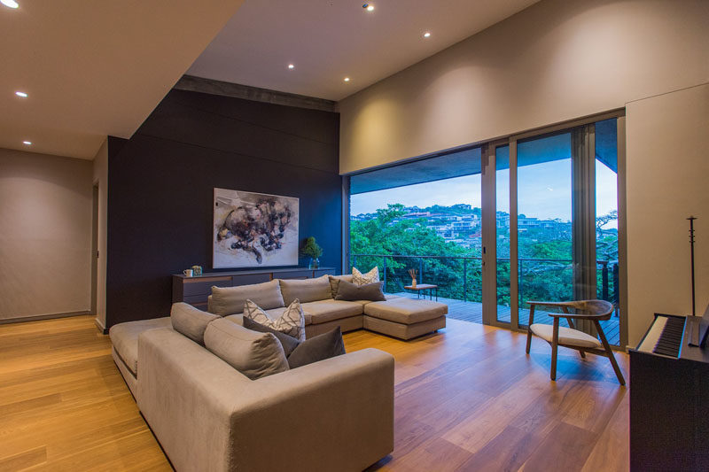 This modern living room features a dark accent wall that highlights the artwork, while sliding glass doors open to a balcony with treetop views. #LivingRoom #DarkAccentWall