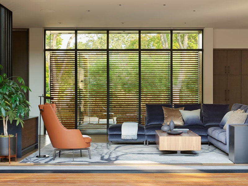 A series of metal and wood sunshades, like in this modern living room, provide the interiors with protection from the sun, without giving up the views. #WoodScreens #LivingRoom #ModernInterior