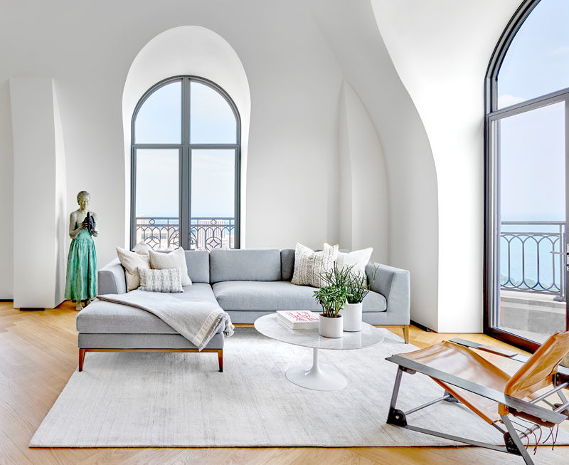 Living Room Ideas - This modern living room features minimal furnishings in soft colors, to create a relaxing and calm atmosphere. Arched windows and vaulted ceilings help to keep the space bright and open. #LivingRoomIdeas #ModernInterior #LivingRoom
