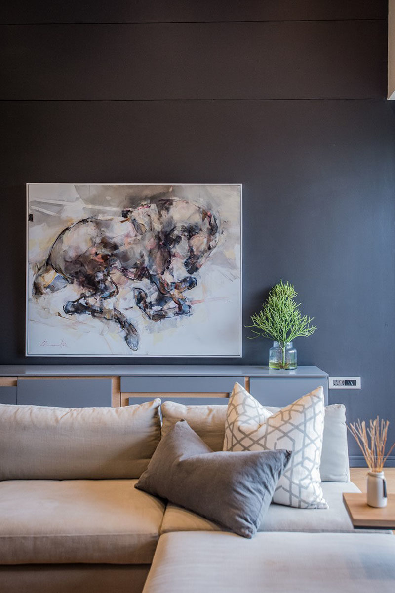 This modern living room features a dark accent wall that helps to make the artwork and light colored furniture stand out. #LivingRoom #DarkWall